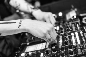 person with tattoos on their arms adjusting the knobs of a mixing board